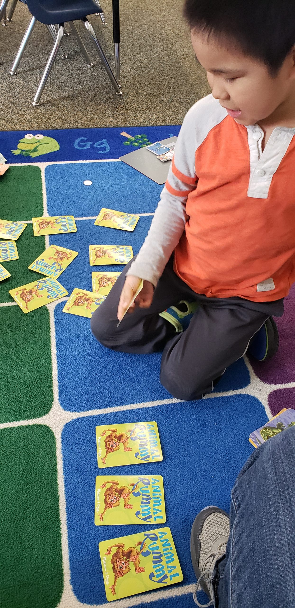 Elementary student playing a memory card game on a colorful carpet.