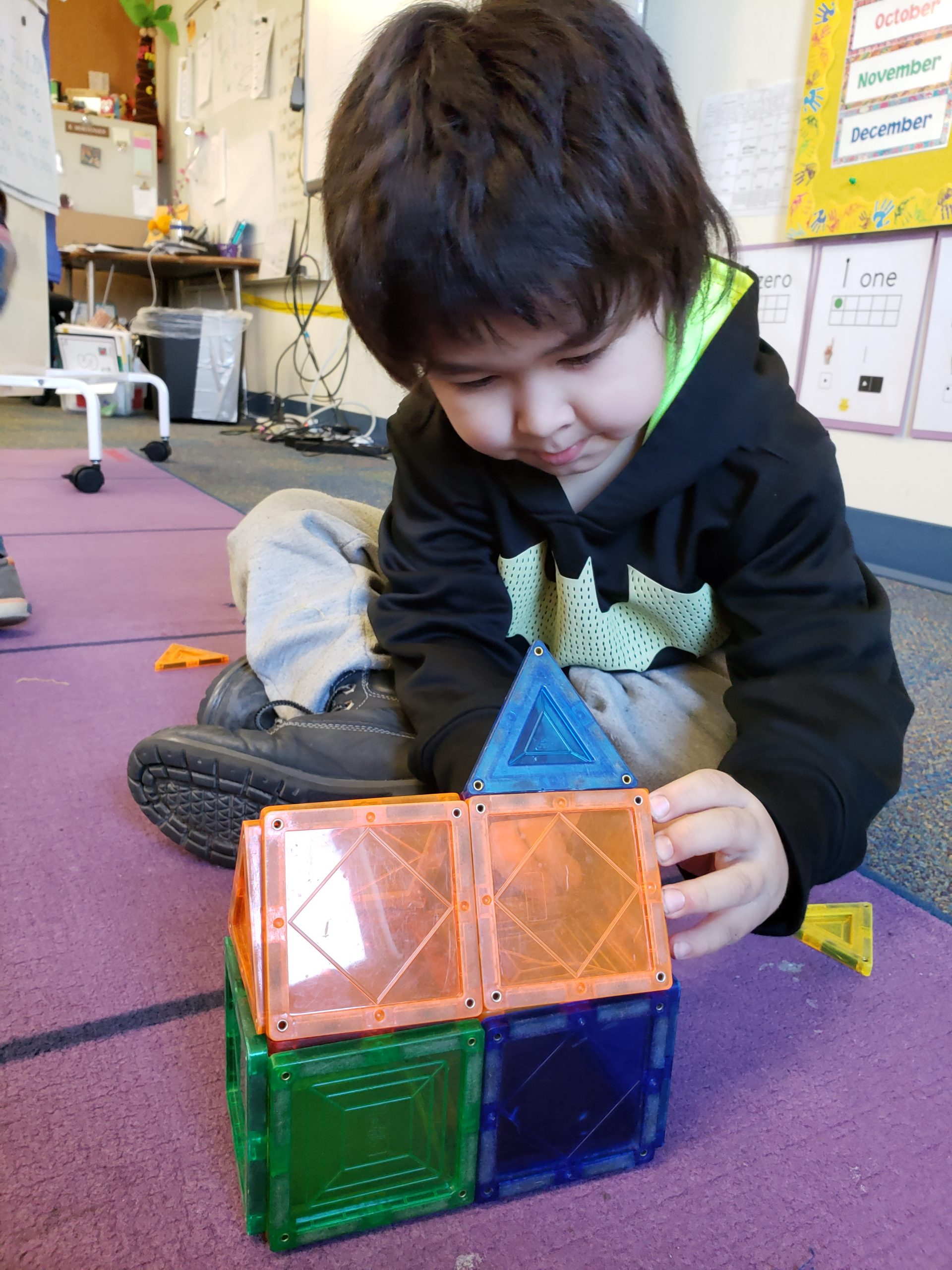 A young boy is playing with magnetic shapes to make a 3D house on the floor.
