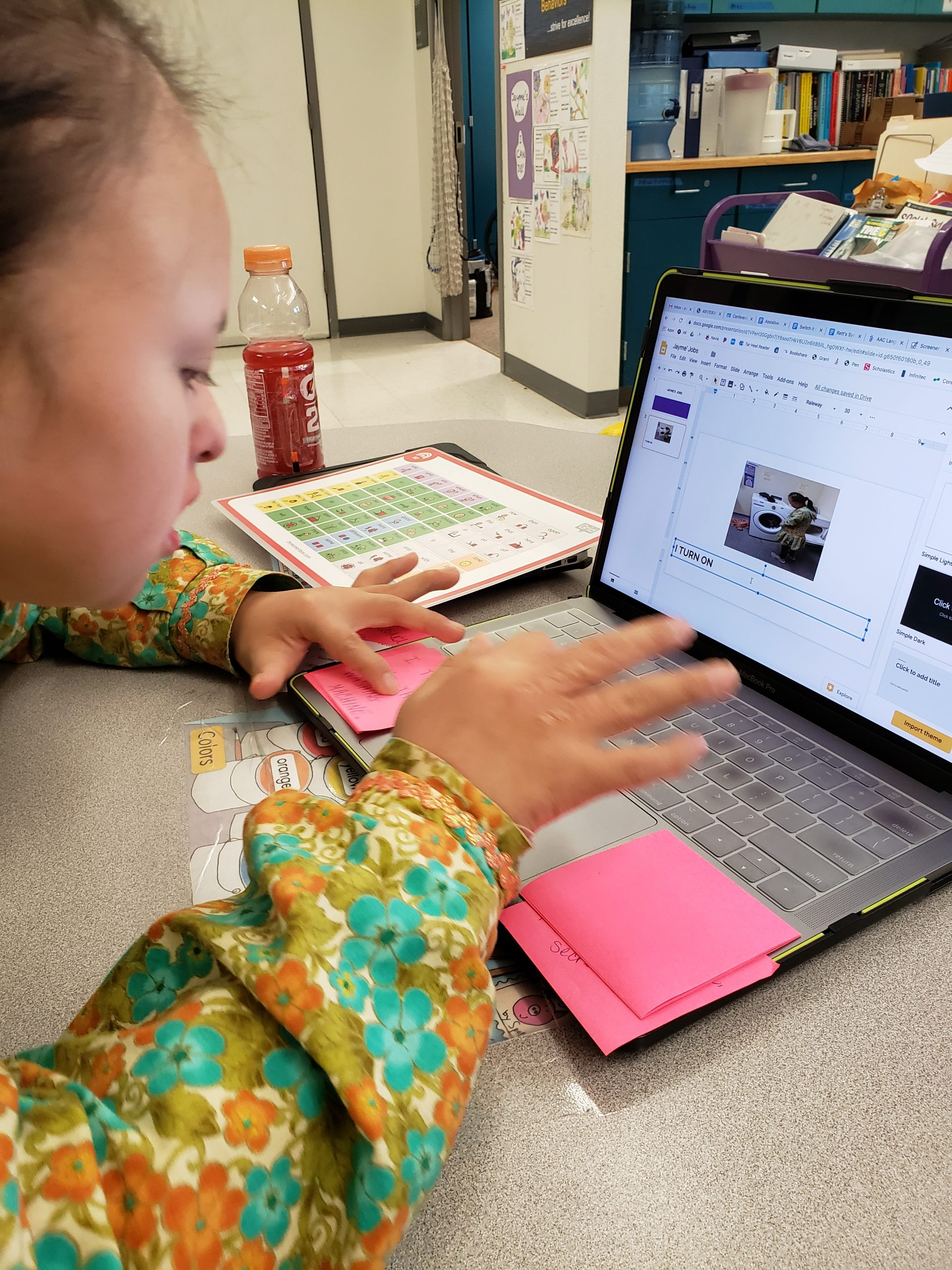 A middle school student is typing a sentence on the computer with visual supports on post it notes.
