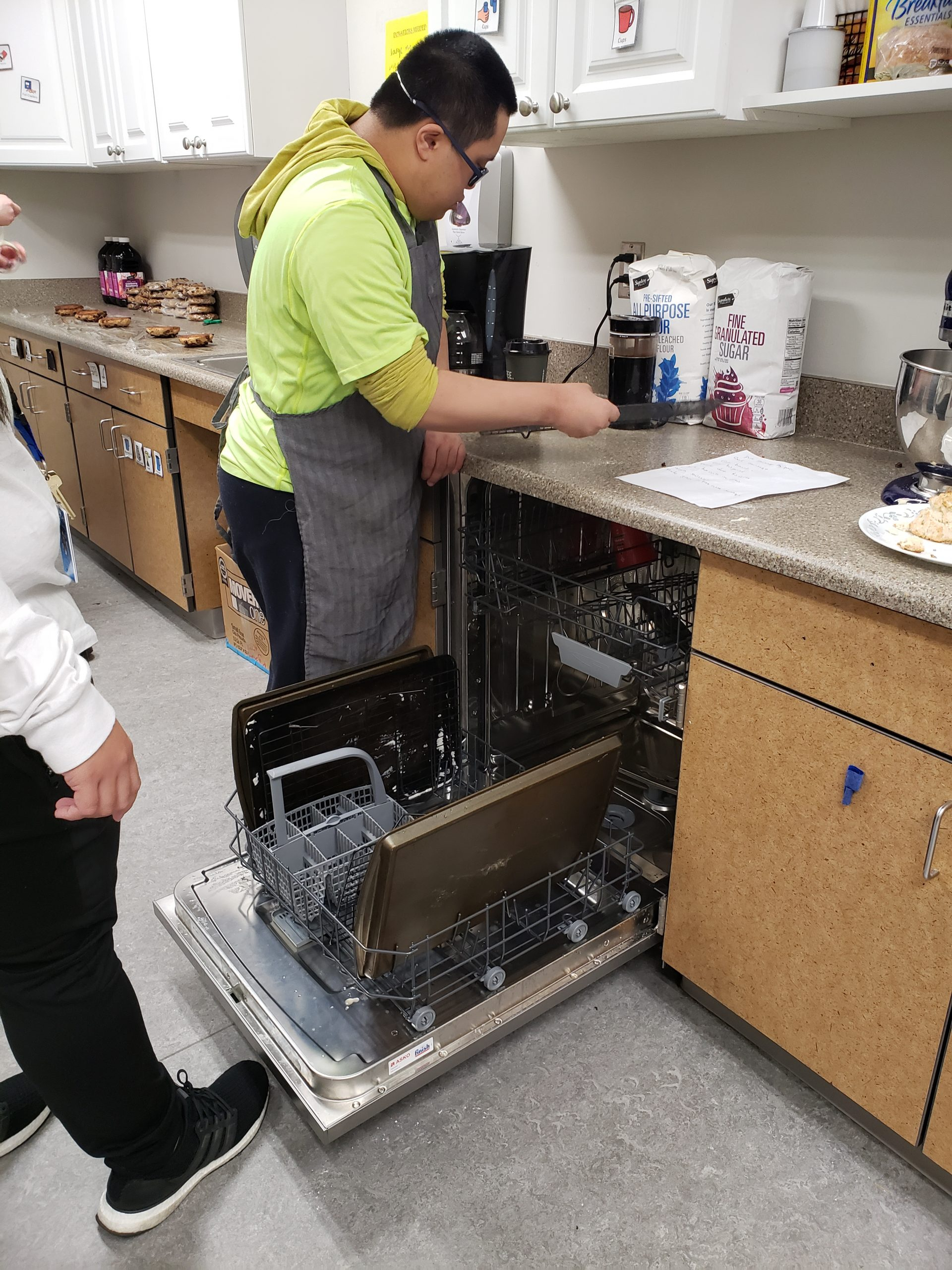 An adult male is learning job skills while loading the dishwasher after cooking class.