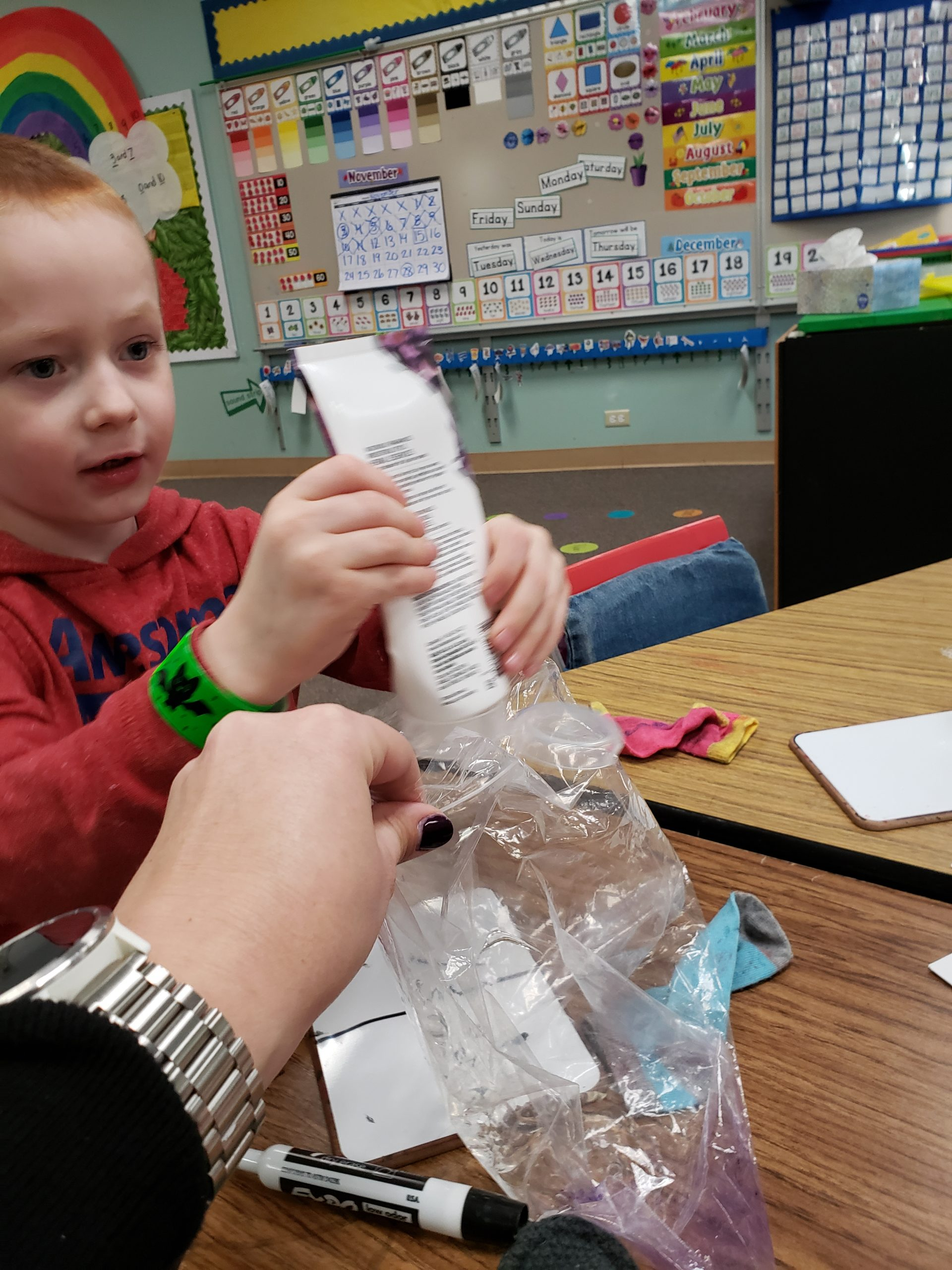 A young boy is squeezing hair gel from a tube into a ziploc bag with the help of an adult.