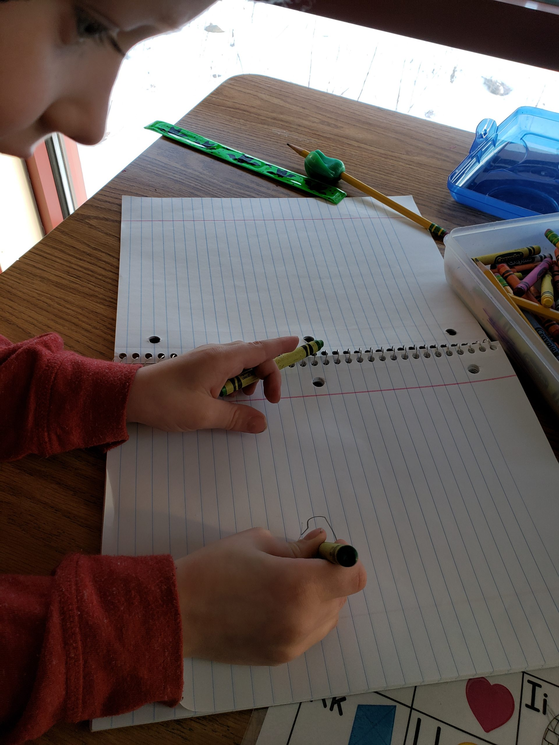 A young boy is drawing in a notebook with a crayon in each hand.
