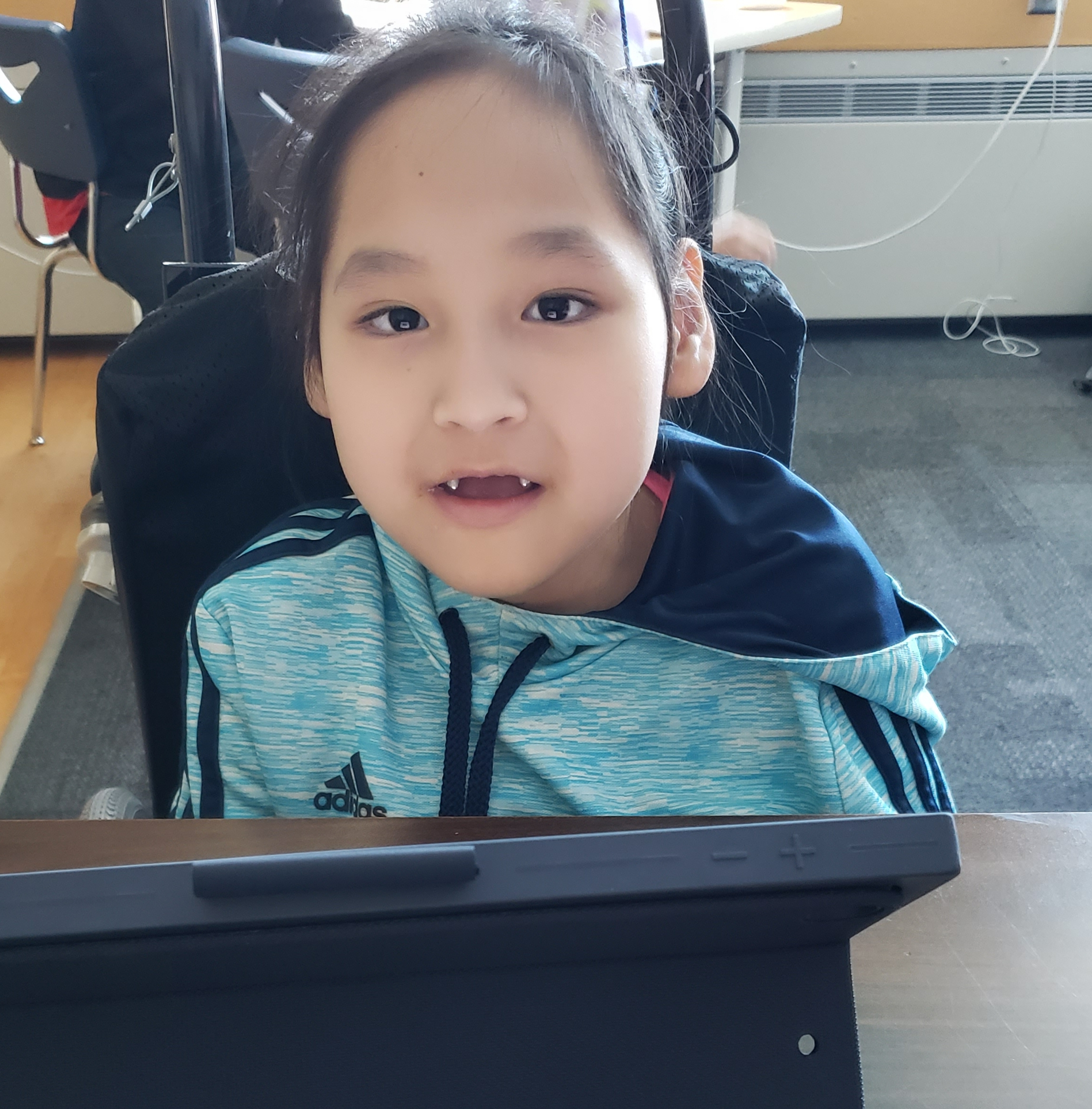 A young girl in a wheelchair looks up from the iPad as she is working.