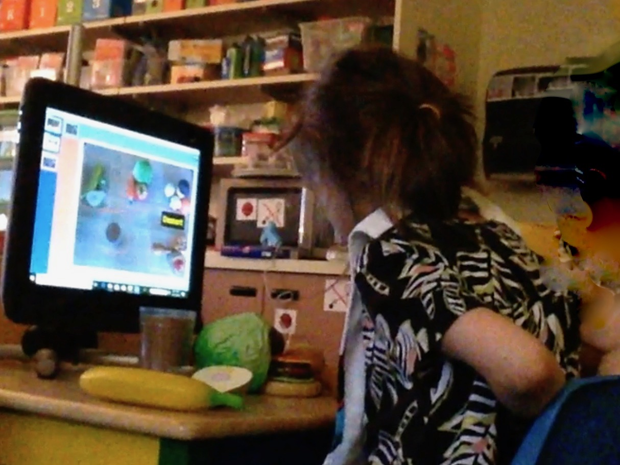 A young girl is sitting at a desk, using eye gaze to interact with the computer.