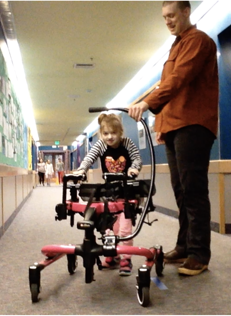 A young girl is learning how to walk with special equipment and a teacher.