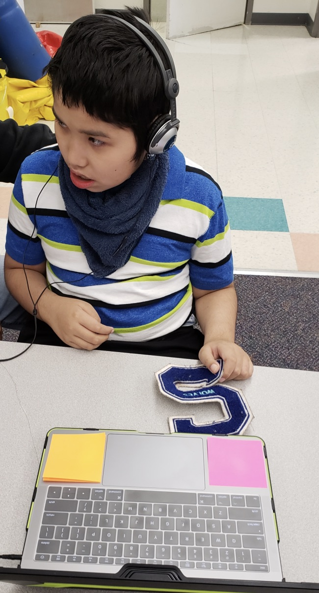 A young boy wearing headphones is listening to a book on the computer as he looks into the hallway.