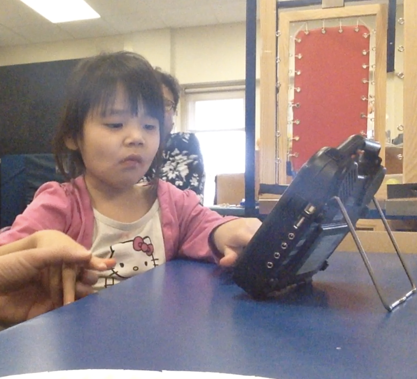 A young girl is learning how to communicate with an AAC device with the help of her teacher.