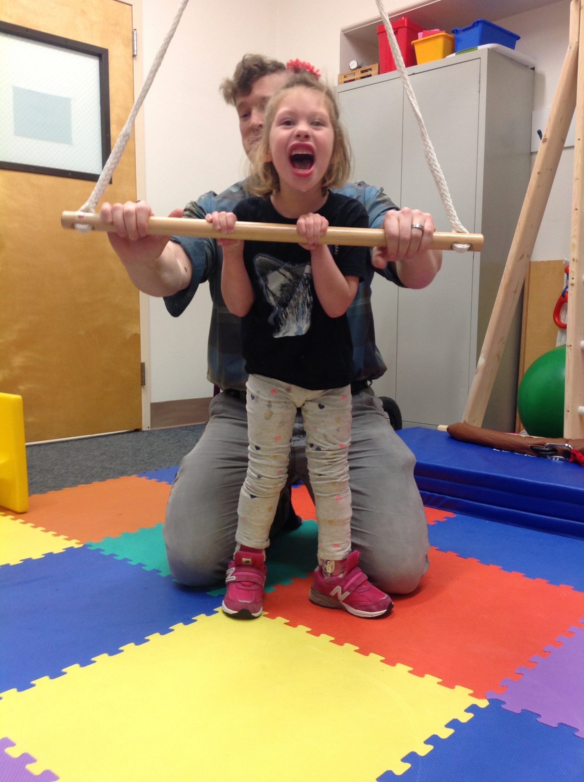 A young girl is using bar supports to stand tall while her teacher kneels behind her.