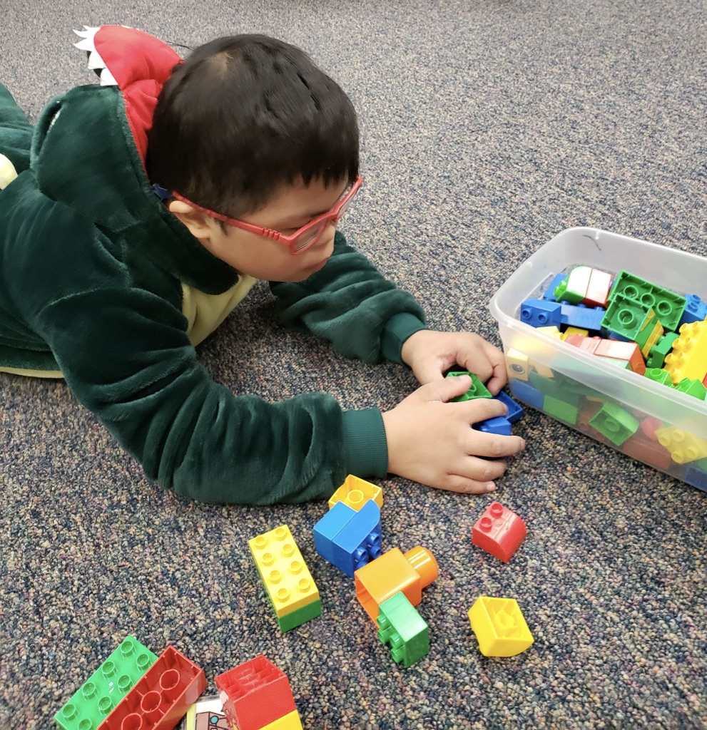 Young student with Down Syndrome playing with legos on the floor.